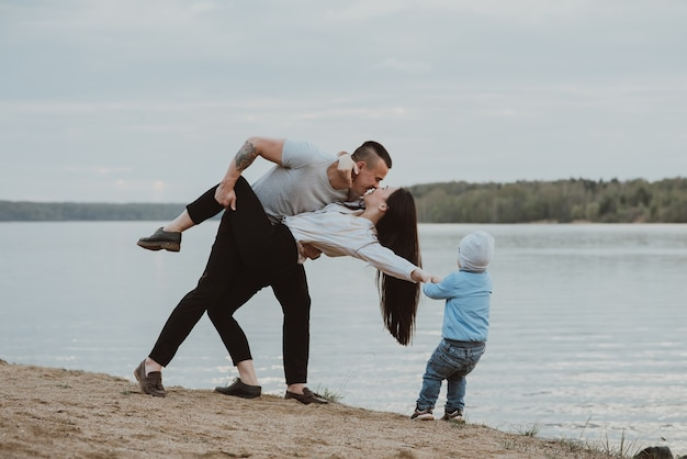 Beautiful family with their son near a river