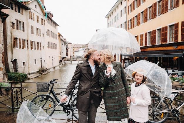 안시에서 비오는 날씨에 우산과 아름다운 가족. 프랑스 가족은 빗속에서 산책합니다.