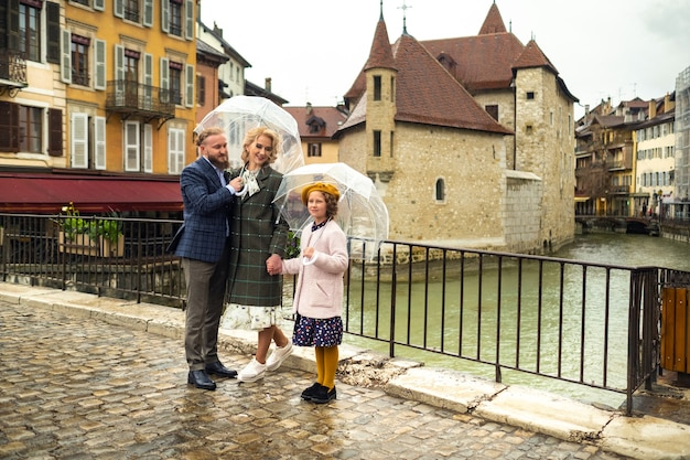 Beautiful family with umbrellas in rainy weather in annecy by a river