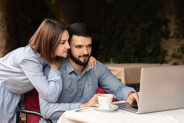 Beautiful family working from home, man and woman in love embracing, working on laptop indoors