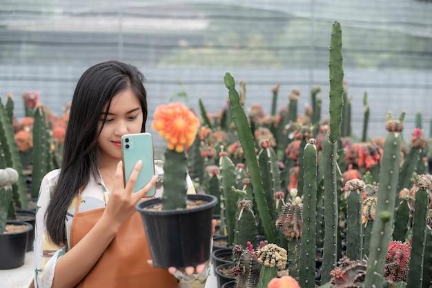 선인장 농장 집에서 냄비에 태블릿으로 선인장 식물의 품질을 확인하는 아름다운 농부.