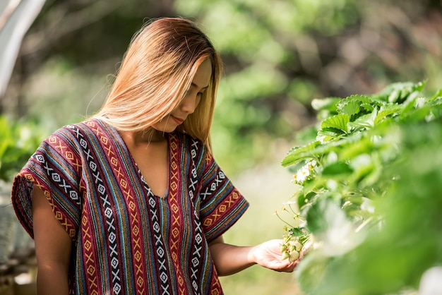 Beautiful farmer woman checking strawberry farm