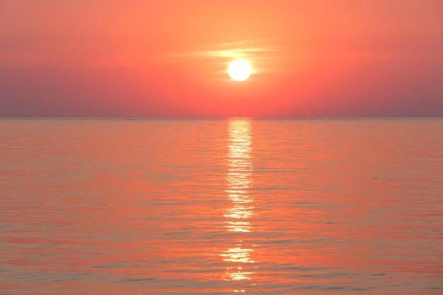 表面に日の出と太陽の軌跡がある美しい魅力的な朝の海の景色。