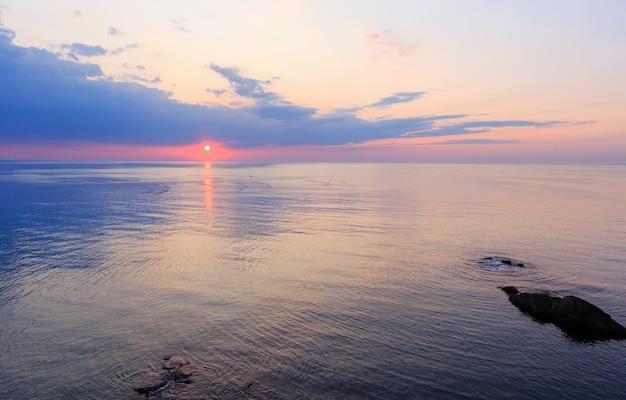 日の出、表面の太陽の跡、漁網のある美しい魅惑的な朝の海の景色。