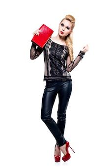 明るいメイクで美しいファッション金髪女性。赤い色のスタイリッシュなアクセサリーを持つかわいい女の子モデル。