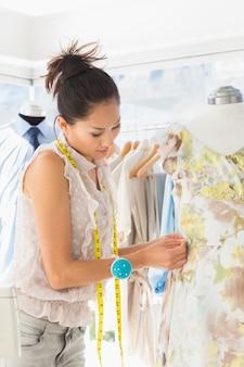 Beautiful fashion designer working on dress at the studio