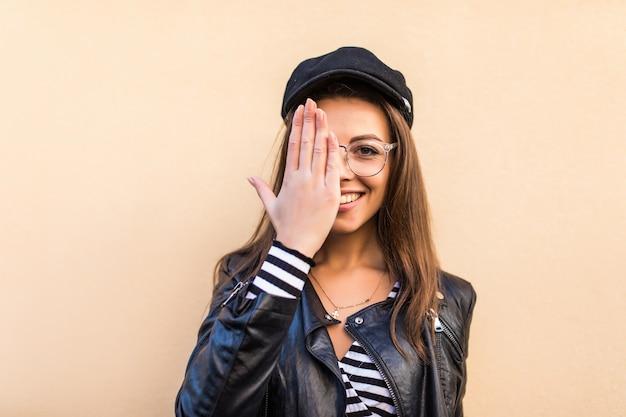 革のジャケットと黒い帽子の美しいファッションの女の子は、明るい黄色の壁に隔離された彼女の手で彼女の顔の目を覆います