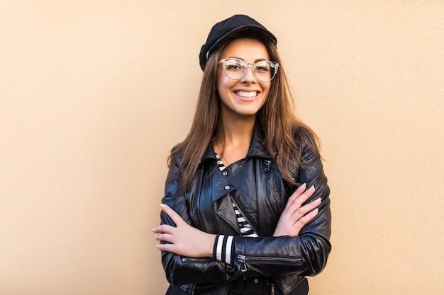 革のジャケットと黒い帽子の美しいファッションの女の子は、明るい黄色の壁に分離された腕を組んで保持します。