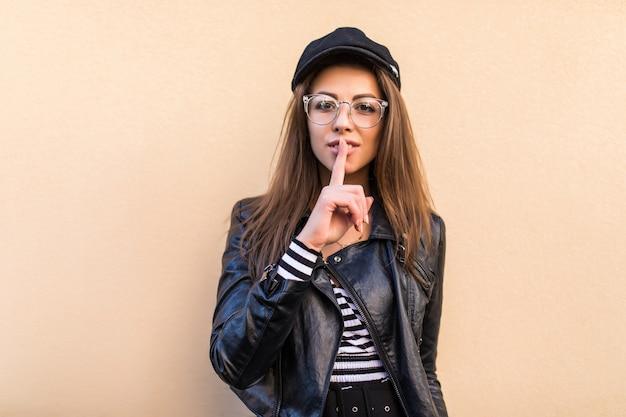 薄黄色の壁に分離された革のジャケットと黒い帽子の美しいファッションの女の子
