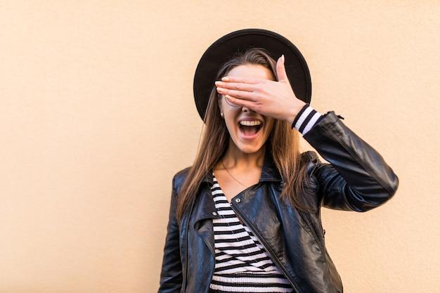 Bella ragazza di moda in giacca di pelle e cappello nero si copre il viso con la mano isolata sul muro giallo chiaro