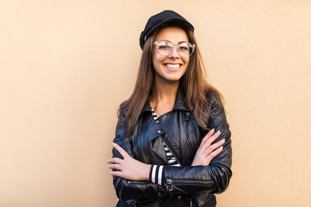 Bella ragazza di modo in giacca di pelle e cappello nero tenere le braccia incrociate isolato sul muro giallo chiaro