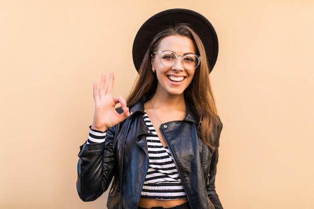 La bella ragazza di modo in giacca di pelle e cappello nero mostra il segno giusto isolato sulla parete gialla chiara
