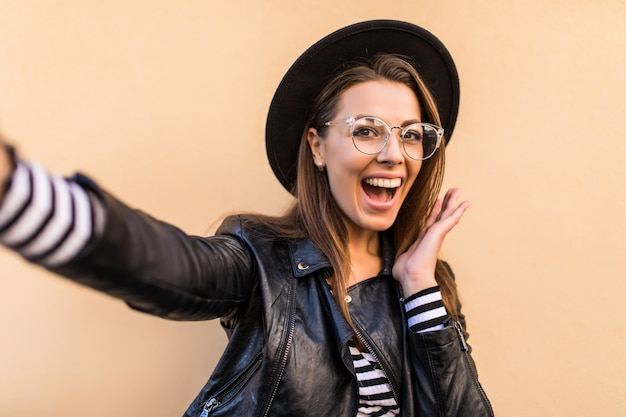 Bella ragazza di moda in giacca di pelle, occhiali trasparenti e cappello nero fa selfie isolato sul muro giallo chiaro