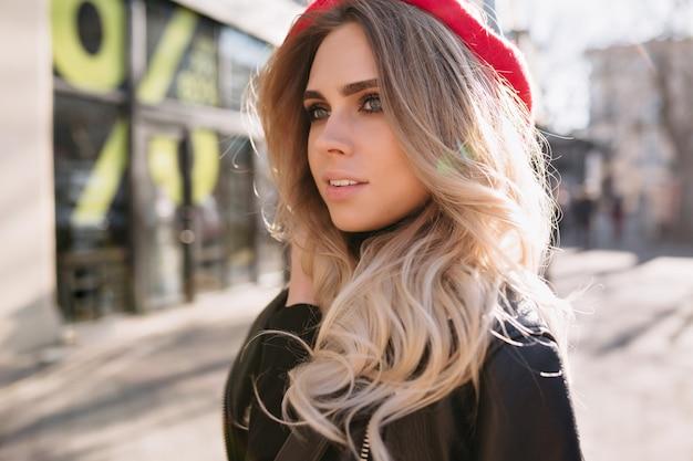 Bella ragazza di moda con capelli biondi lunghi vestito giacca di pelle e cappello rosso cammina per strada alla luce del sole con felici emozioni vere.