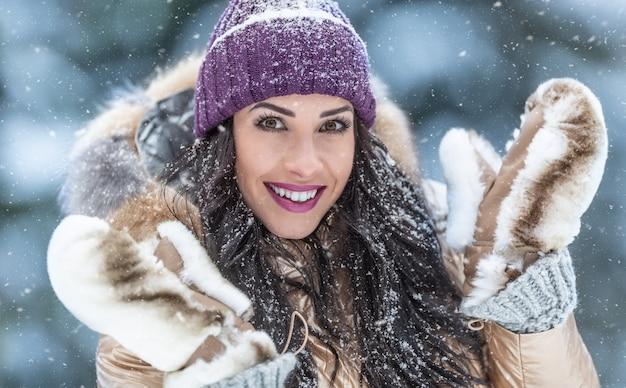 美しいファッションを愛する女性は、雪の日に屋外で毛皮のコートと毛皮の手袋を着用します。