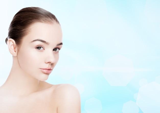 Beautiful fashion model girl natural makeup spa skin care portrait on blue bokeh background