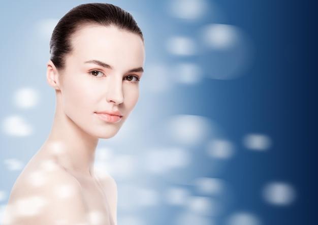 Beautiful fashion model girl natural makeup spa skin care portrait on dark blue bokeh background