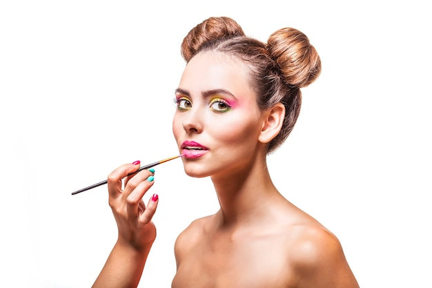 메이크업 아티스트가 흰색 표면에 메이크업, 립글로스를 적용하는 아름다운 패션 모델 소녀