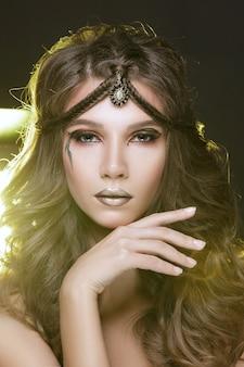 Beautiful fashion model girl with golden makeup.