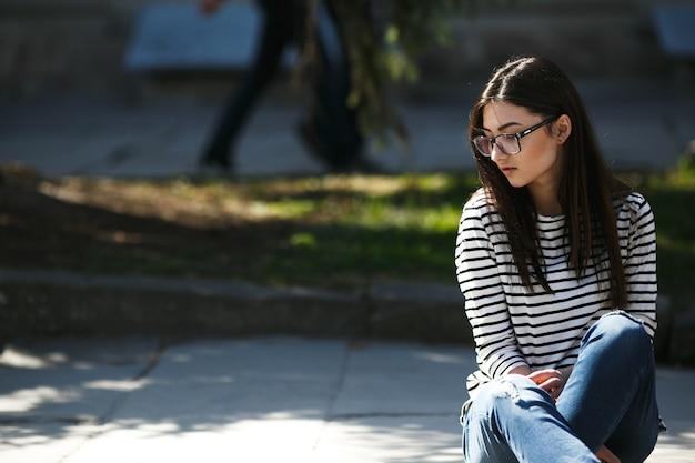 Bella modella con gli occhiali si siede