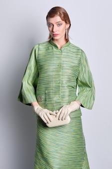 Красивая фотомодель в шелковом зеленом пиджаке и юбке со старомодной прической
