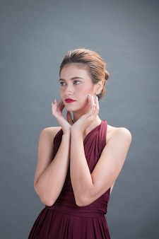 Красивая модель, показывающая и касающаяся, чтобы представить ее лицо