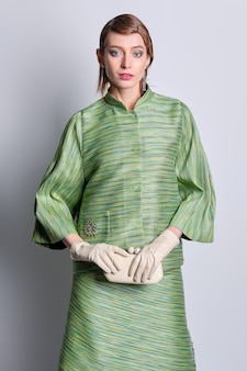 Beautiful fashion model in silk green jacket and skirt with old fashioned hairstyle