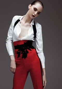 Beautiful fashion model wearing red pants and white shirt on grey background