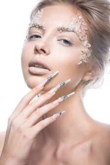 Красивая манекенщица с длинными ногтями, креативным макияжем и дизайном маникюра.