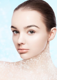 Beautiful fashion model with natural makeup spa skin care portrait on blue bokeh background with shiny glitter stars on neck