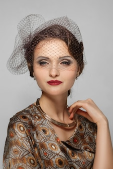 Beautiful fashion model with red mat lips and veil over eyes in silk dress. clean fresh face of pretty girl with natural makeup.