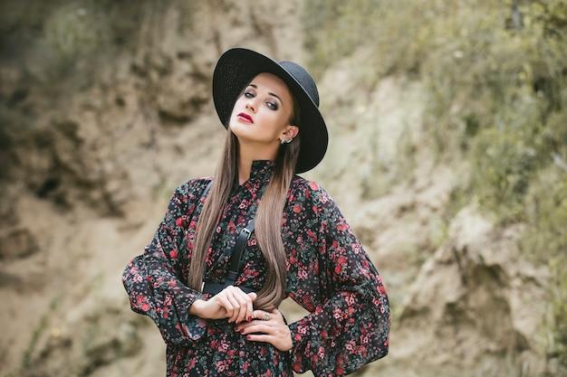 Красивая фотомодель женщина с макияжем и маскарадным платьем снаружи на фоне песка