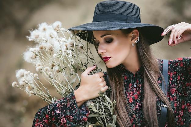 砂の背景に化粧とデザインの凝った服の外で美しいファッションモデルの女性