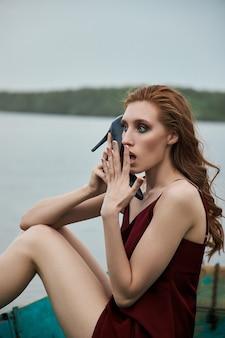 아름 다운 패션 빨간 머리 여자는 보트에 앉아. 호수에 나무 보트에 빨간 vinous 드레스에 아름다움 로맨틱 초상화 소녀