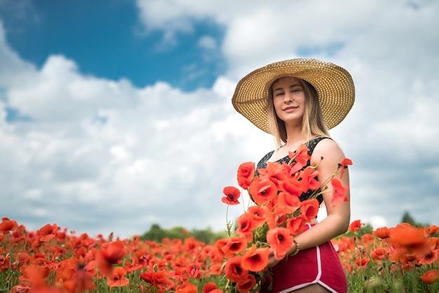 뜨거운 여름 날 양 귀 비 필드에 아름 다운 패션 십 대 소녀는 자연을 즐길 수 있습니다.