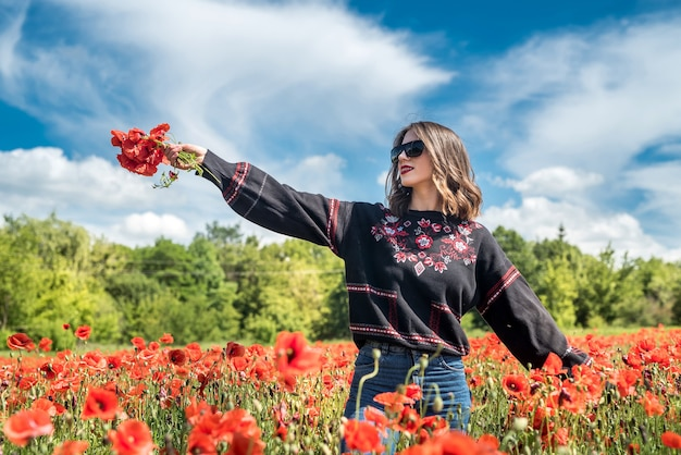 夏の美しいファッションティーンエイジャーの女の子ポピーフィールドは自然を楽しむ