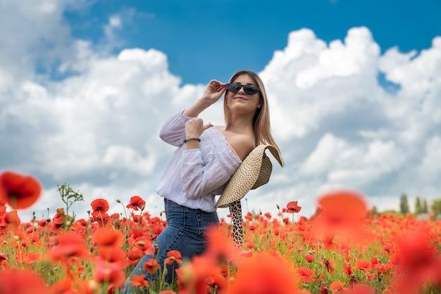 여름에 아름 다운 패션 십 대 소녀 양 귀 비 필드 자연을 즐길 수