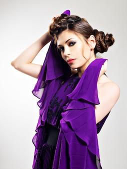 ピグテールのデザイン、スタジオでポーズと紫色のロングドレスの髪型の美しいファッションの女性