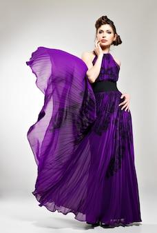 ピグテールのデザイン、スタジオでポーズと紫のロングドレスの髪型の美しいファッションの女性