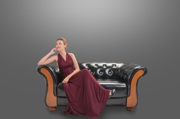 Красивая женщина модель модель сидит и улыбается позирует на диване
