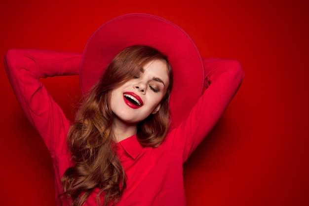 Beautiful fashion woman on a red background in a red hat with red lipstick on her lips