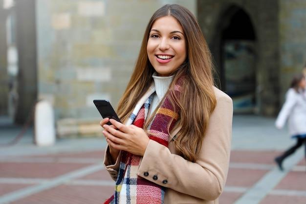 Красивая модная женщина с помощью смартфона, глядя в камеру на улице на улице города