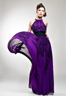 Bella donna di modo in acconciatura abito lungo viola con disegno di trecce, pose in studio