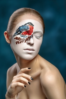 Beautiful fashion woman with face art in winter style. textural makeup.