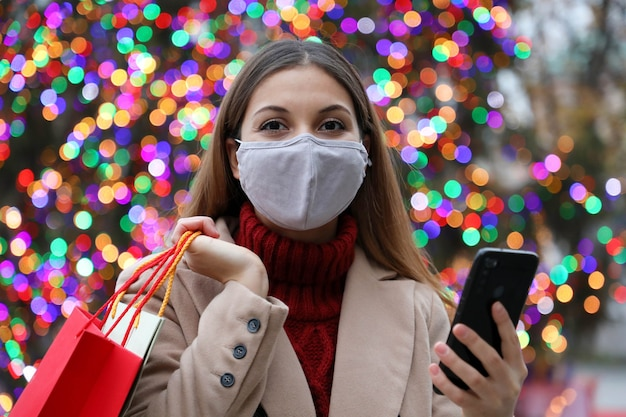 Beautiful fashion woman with face mask and shopping bags purchasing online with smart phone in the street with christmas tree lights