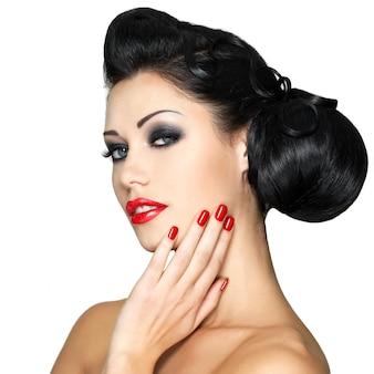 빨간 입술, 손톱 및 창조적 인 헤어 스타일을 가진 아름 다운 패션 여자-흰 벽에 고립