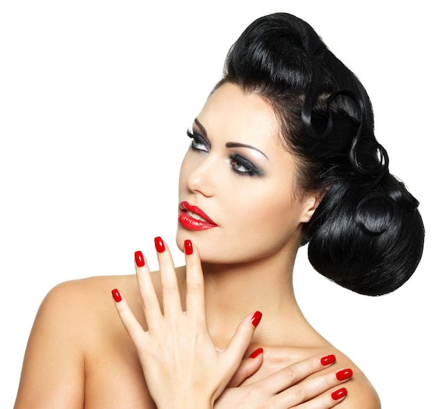 Beautiful fashion woman with red lips, nails and creative hairstyle - isolated on white wall