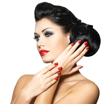 Beautiful fashion woman with red lips, nails and creative hairstyle