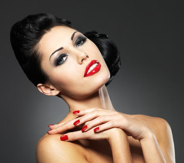 Красивая модная женщина с красными ногтями, креативной прической и макияжем