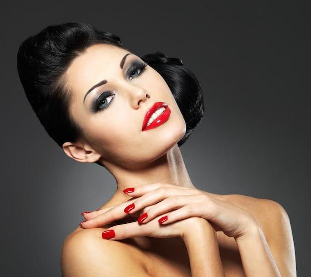 Bella donna di moda con unghie rosse, acconciatura creativa e trucco